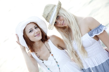 Two beautiful young girlfriends in hat on the beach of Black Sea. Sea and sunlight is on background.  photo