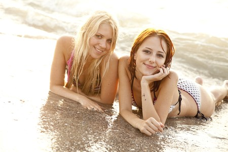 Two beautiful young girlfriends in bikini on the beach of Black Sea. Sea and sunlight is on background. photo