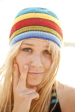 f4e15c41bc8 Beautiful young blonde girl in rastafarian hat. Sunlight is on background.
