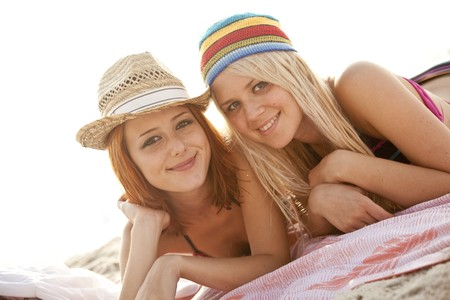Two beautiful young girlfriends in bikini on the beach of Black Sea.Sunlight is on background. photo