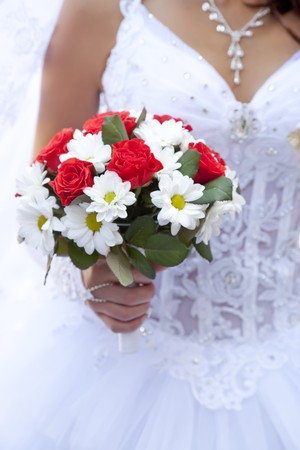 Bride holding beautiful red roses wedding flowers bouquet  photo