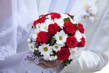 Bridegroom and bride holding beautiful red roses wedding flowers bouquet