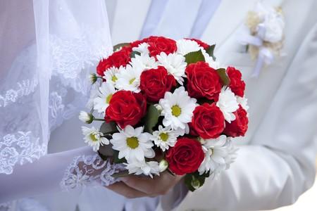 Bruidegom en de bruid met prachtige rode rozen bruiloft bloemen boeket