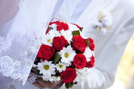 Bridegroom and bride holding beautiful red roses wedding flowers bouquet Stock Photo - 7690470