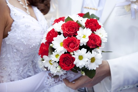 suitor: Bridegroom and bride holding beautiful red roses wedding flowers bouquet