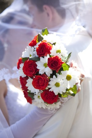 suitor: Sposo e la sposa baciare e detenzione belle rose rosse bouquet di fiori matrimonio  Archivio Fotografico