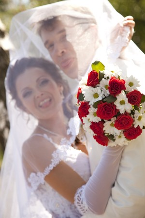 suitor: Bridegroom and bride holding beautiful red roses wedding flowers bouquet Stock Photo