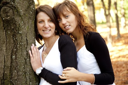 two face: Two beautiful sisters in the park near tree. Stock Photo
