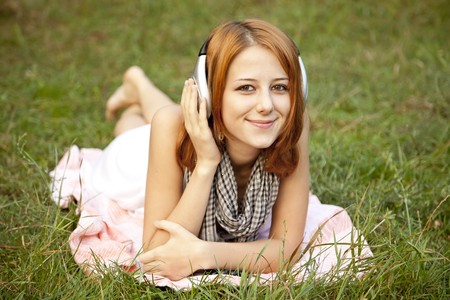 Young fashion girl with headphone lying at green grass at park. Stock Photo - 7766856
