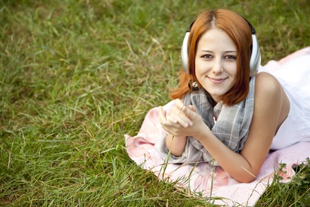 Young fashion girl with headphone lying at green grass at park. photo
