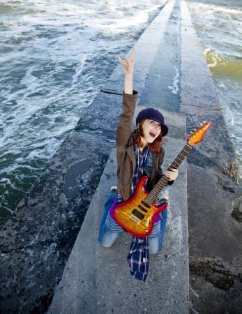 Rothaarige Mädchen Spiel auf Gitarre bei windigen Tag.