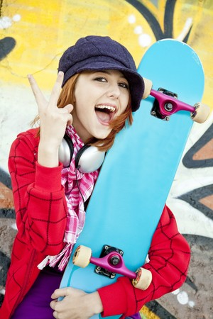Closeup portrait of a happy young girl with skateboard and graffiti on background photo