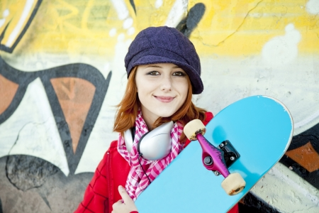Closeup portrait of a happy young girl with skateboard and graffiti on background Stock Photo - 7767020