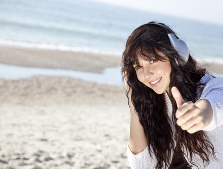 Pretty young woman with headphone on beach Stock Photo - 7767163