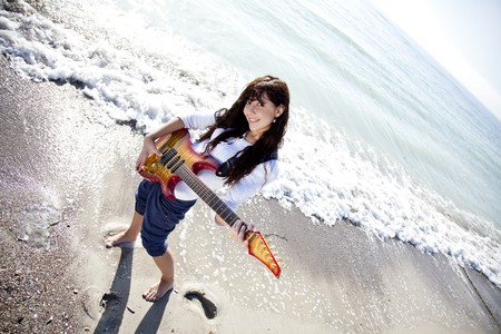 Pretty young woman with guitar on beach photo
