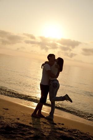 besos apasionados: Pareja bes�ndose en la salida del sol en la playa.  Foto de archivo