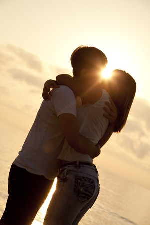 Couple kissing in sunrise at the beach. photo