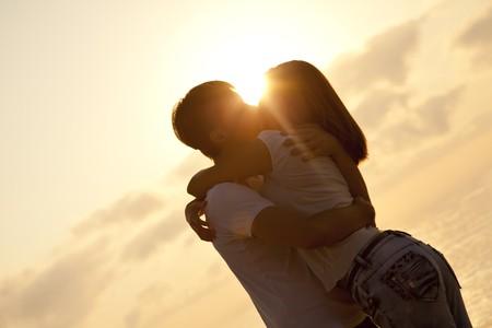 novios besandose: Pareja bes�ndose en la salida del sol en la playa.  Foto de archivo