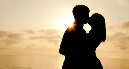 passionate embrace: Couple kissing in sunrise at the beach.