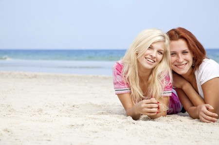 Two girl friends lying down at the beach. photo