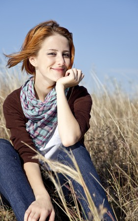 women in jeans: Portrait of happy red-haired girl on autumn grass. Stock Photo