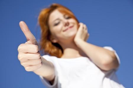 ok symbol: Ritratto di una ragazza dai capelli rossi in bianco che mostra il simbolo della mano OK.