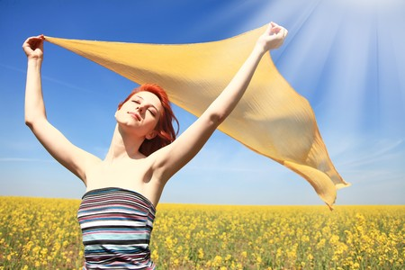 adult rape: Young woman with open arms keep yellow silk on wind at rape field. Shine from left corner.