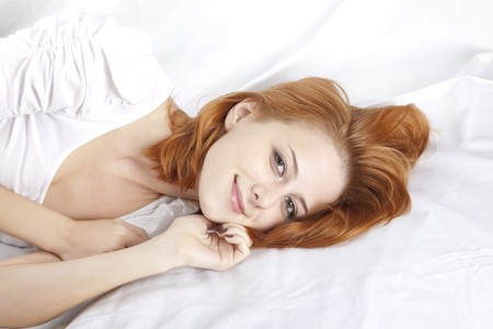 luxuriate: Pretty red-haired sleeping woman in white nightie lying in the bed