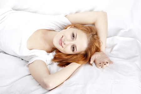 nightie: Pretty red-haired sleeping woman in white nightie lying in the bed