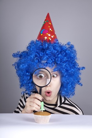 Funny girl with blue hair and striped knitted jacket looking through loupe at cake for birthday with one candle. Stock Photo - 8083702