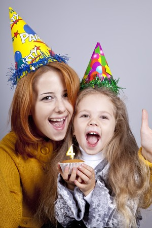 comically: Two sisters four and eighteen years old at birthday. Studio shot. Stock Photo