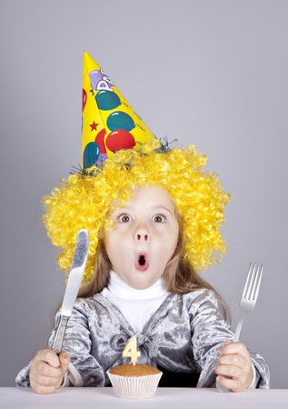 comically: Portrait of young girl at birthday with cake. Studio shot.
