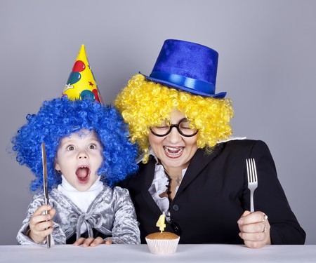 Mother and child in funny wigs and cake at birthday. Studio shot. Stock Photo - 8083812