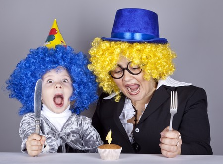 comically: Mother and child in funny wigs and cake at birthday. Studio shot.