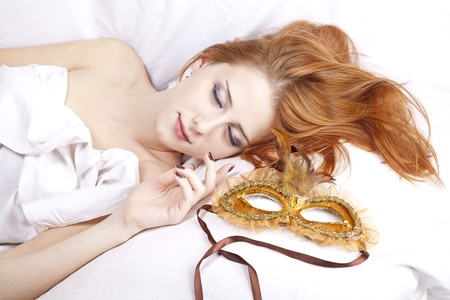 Pretty red-haired sleeping woman in white lying in the bed near carnival mask. photo