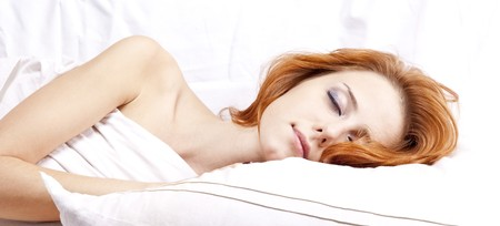 nightie: Pretty red-haired sleeping woman in white nightie lying in the bed Stock Photo