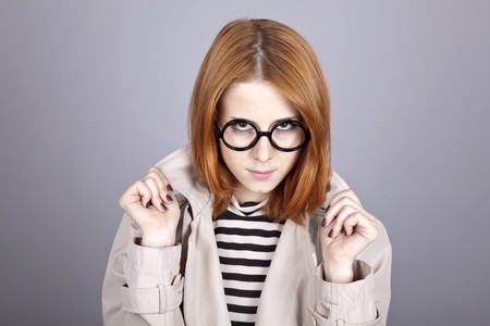 comically: Young red-haired girl in glasses and cloak. Studio shot.