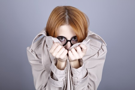comically: Hiding red-haired girl in glasses and cloak. Studio shot.