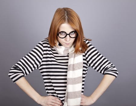 comically: Angry red-haired girl in glasses and scarf. Studio shot.