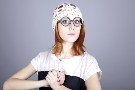 comically: Portrait of funny girl in glasses and white cap. Studio shot.