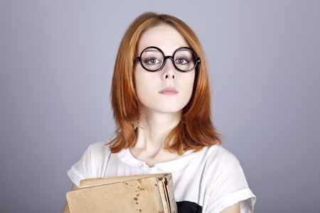 comically: Funny red-haired girl with old book. Studio shot.  Stock Photo