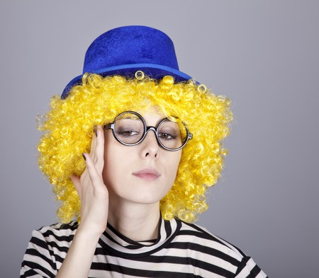 comically: Portrait of yellow-haired girl in blue cap and striped knitted jacket. Studio shot.