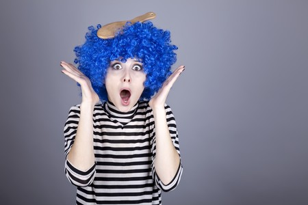 comically: Surprised blue hair girl with stuck comb. Studio shot.