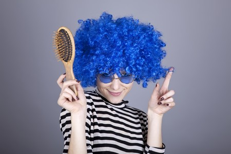comically: Coquette blue-hair girl with comb. Studio shot.