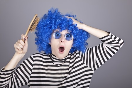 comically: Surprised blue hair girl with comb. Studio shot.