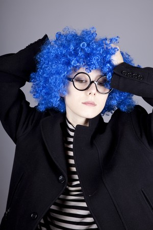comically: Funny fashion blue-hair girl in glasses and black coat. Studio shot. Stock Photo