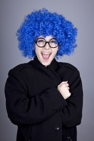 comically: Funny blue-hair girl in glasses and black coat. Studio shot. Stock Photo