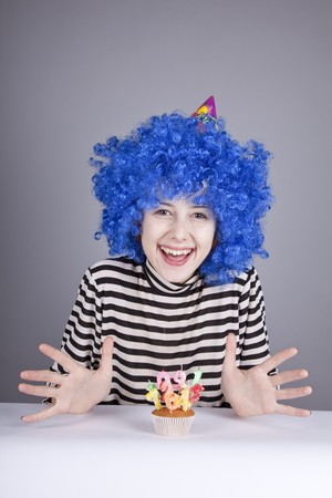 comically: Funny blue-hair girl with cake. Studio shot.