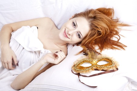 Pretty red-haired woman in white lying in the bed near carnival mask.  photo