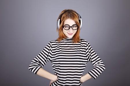 Funny girl with headphone and glasses. Studio shot. photo